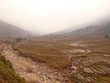 Rice terraces stretch from the river's edge to the peaks above.